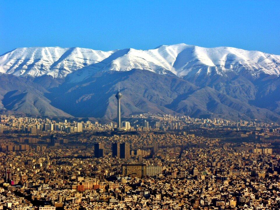 Na zdjęciu rozległe tereny miejskie, zwarta zabudowa, wiele wysokich budynków, tuż za miastem wysokie pasmo górskie wgórnej części ośnieżone.