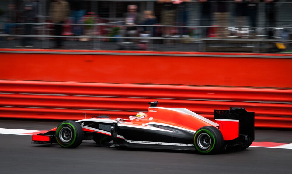 Zdjęcie przedstawia bolid Formuły jeden uchwycony zboku wruchu zsilnie rozmytym tłem. Zbliżenie na centralną część maszyny ikierowcę.