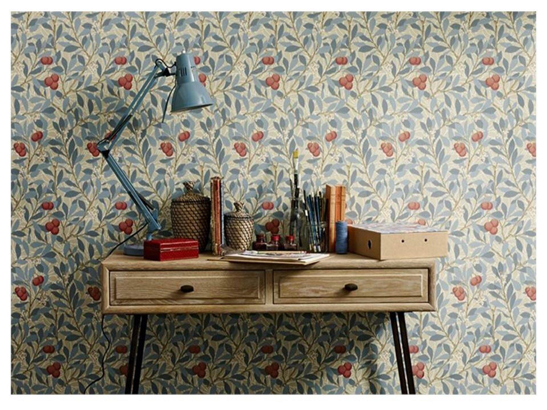 Ilustracja przedstawia tapetę Williama Morrisa we współczesnym wnętrzu. Na tapecie możemy zobaczyć liczne gałęzie, których liście są wkolorze niebieskim. Na poszczególnych gałązkach widnieją również owoce krzewów. Na fotografii widzimy także biurku ustawione pod ścianą, znajduje się na nim lampka, karton, kubek zołówkami oraz kartki papieru.