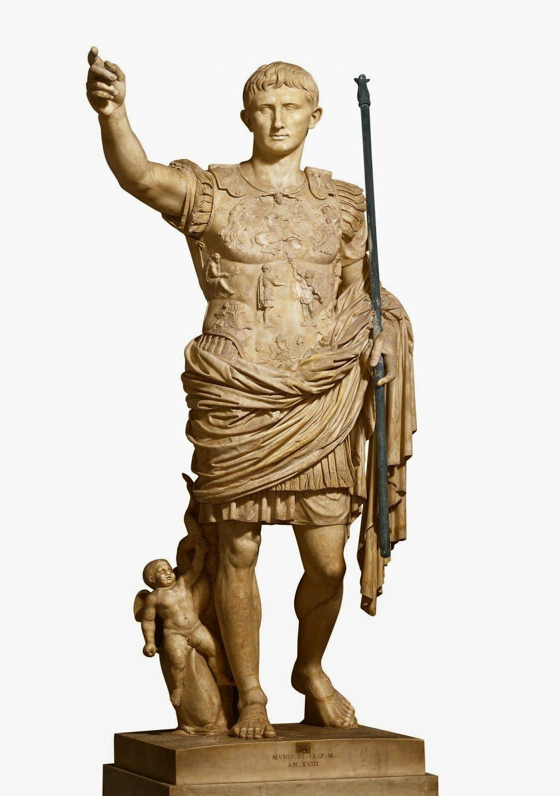"""Ilustracja przedstawia dzieło nieznanego autora """"August zPrima Porta"""". Postać jest ubrana wkrótką tunikę ipancerz. Płaszcz jest owinięty wokół bioder iprzerzucony przez lewe ramię. Prawa ręka jest wyciągnięta do góry,a przy nodze znajduje się amor który siedzi na delfinie. Pancerz cesarza jest bogato zdobiony sfinksami, orłem iróżnymi postaciami. Stoi wkontrapoście zwyciągniętą prawą ręką, ana lewej zwisa płaszcz obiegający biodra."""