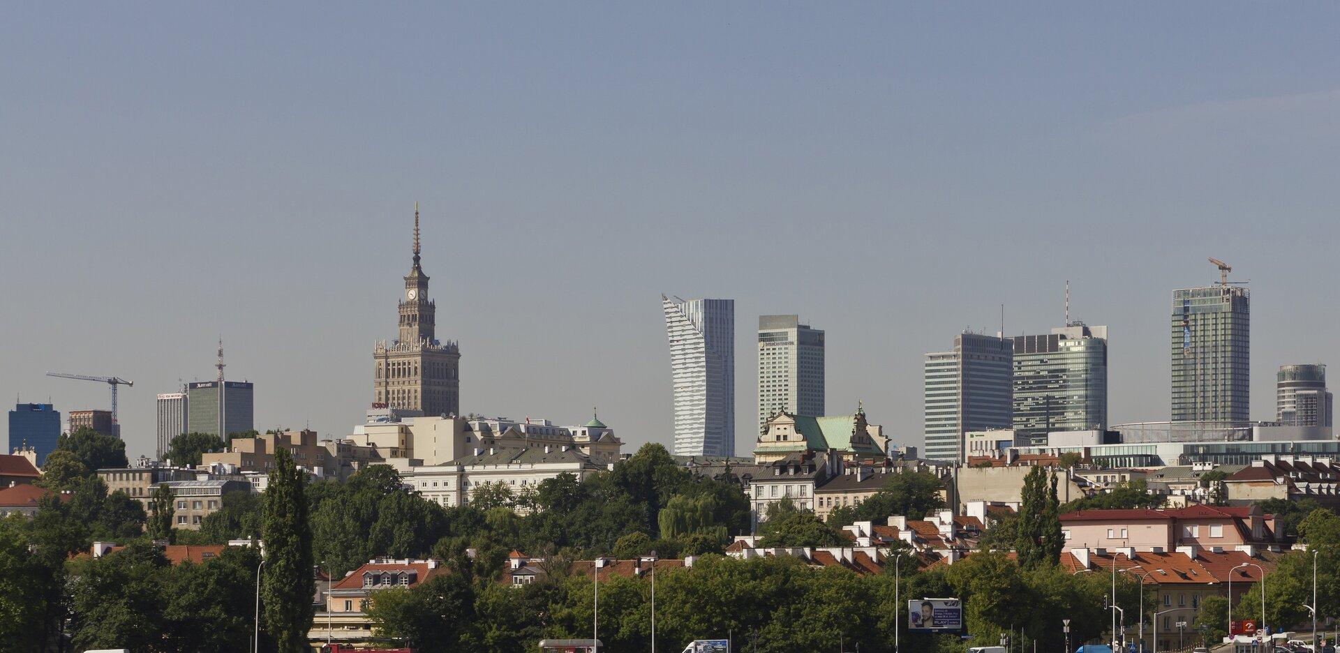 Na zdjęciu nowoczesna zabudowa biurowa. Bardzo wysokie budynki wcentrum miasta.