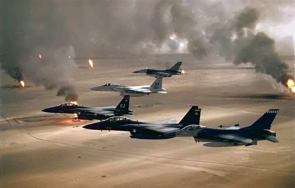 Na zdjęciu lotniczym, kilka samolotów lecących nad pustynnym terenem. Wdole słupy ognia.