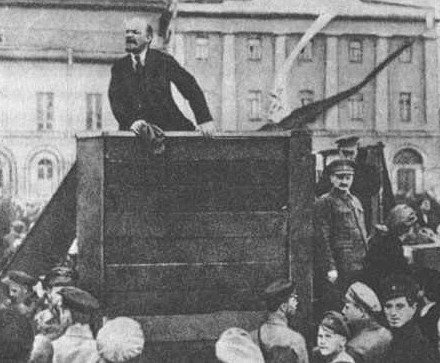 Lenin przemawiający naplacu Czerwonym. Po prawej stronie, oparty otrybunę stoi Lew Trocki Lenin przemawiający naplacu Czerwonym. Po prawej stronie, oparty otrybunę stoi Lew Trocki Źródło: domena publiczna.