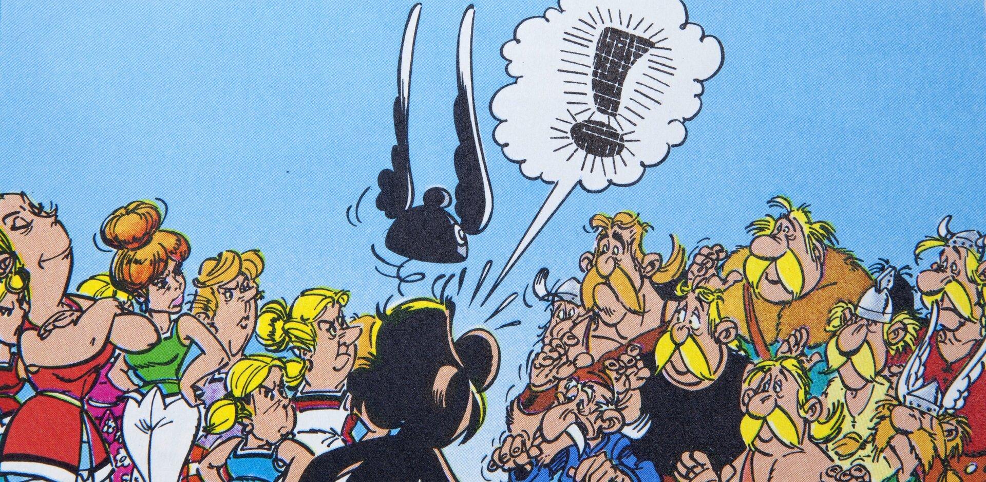 """Ilustracja przedstawia fragment komiksu """"Asterix. Wróżbita"""". Ukazuje tłum ludzi (po lewej kobiety, po prawej mężczyźni) prowadzących spór. Przed nimi stoi odwrócony tyłem do widza Asterix, nad którym unosi się jego hełm ze skrzydełkami. Nad bohaterem znajduje się dymek, wktórym zamiast tekstu jest wykrzyknik."""