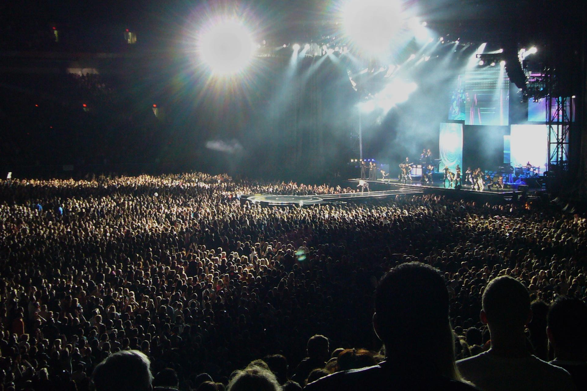 Galeria składa się zpięciu zdjęć prezentujących przykłady imprez masowych. Zdjęcie numer jeden przedstawia wielotysięczny koncert plenerowy nocą. Na pierwszym planie tłum widzów ciągnący się nieprzerwanie aż po najodleglejsze tło. Wgłębi zdjęcia, po prawej stronie, scena muzyczna, ana niej członkowie zespołu muzycznego. Nad sceną kilka dużych reflektorów. Reflektory oświetlają scenę białym światłem. Na pionowej ścianie sceny duże ekrany przedstawiające członków zespołu.