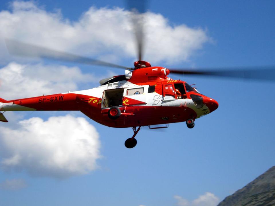 Trzecie zdjęcie to helikopter TOPR. Zdjęcie helikoptera od dołu. 4 śmigła wirują. Helikopter wkolorze czerwonym. Na prawym boku biały pas namalowany skosem. Pas przebiega od dołu kabiny pilona, ukośnie wgórę, sięga do dachu igórnej części ogona helikoptera. Zboku otwarte wejście dla ratowników. Poniżej trzy koła podwozia.