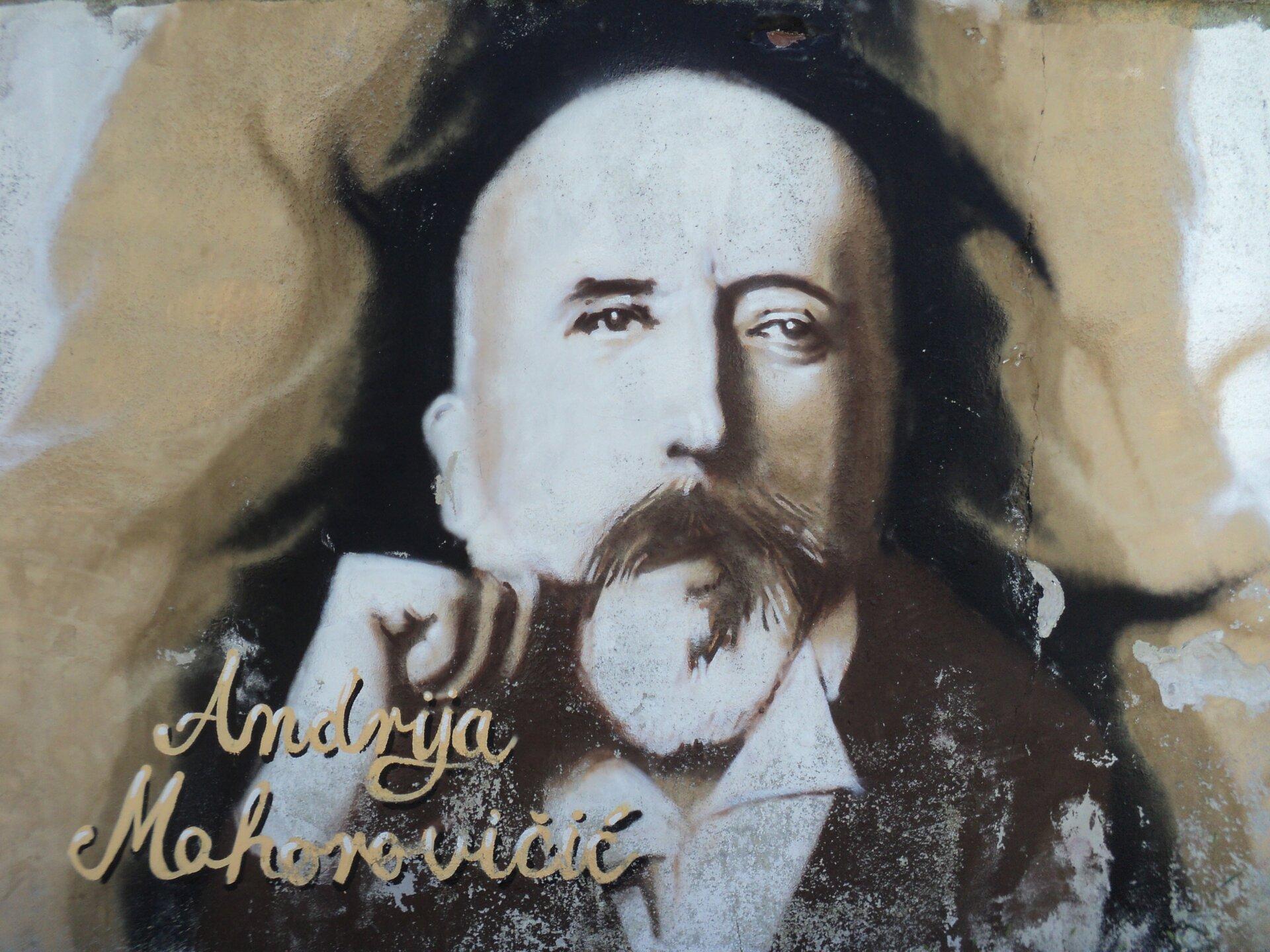 Na portrecie starszy mężczyzna. Jest łysy, ma ciemne wąsy isiwą brodę. Na wysokości twarzy trzyma podniesioną pięść. Zlewej strony napisano Andrija Mohorovičić.