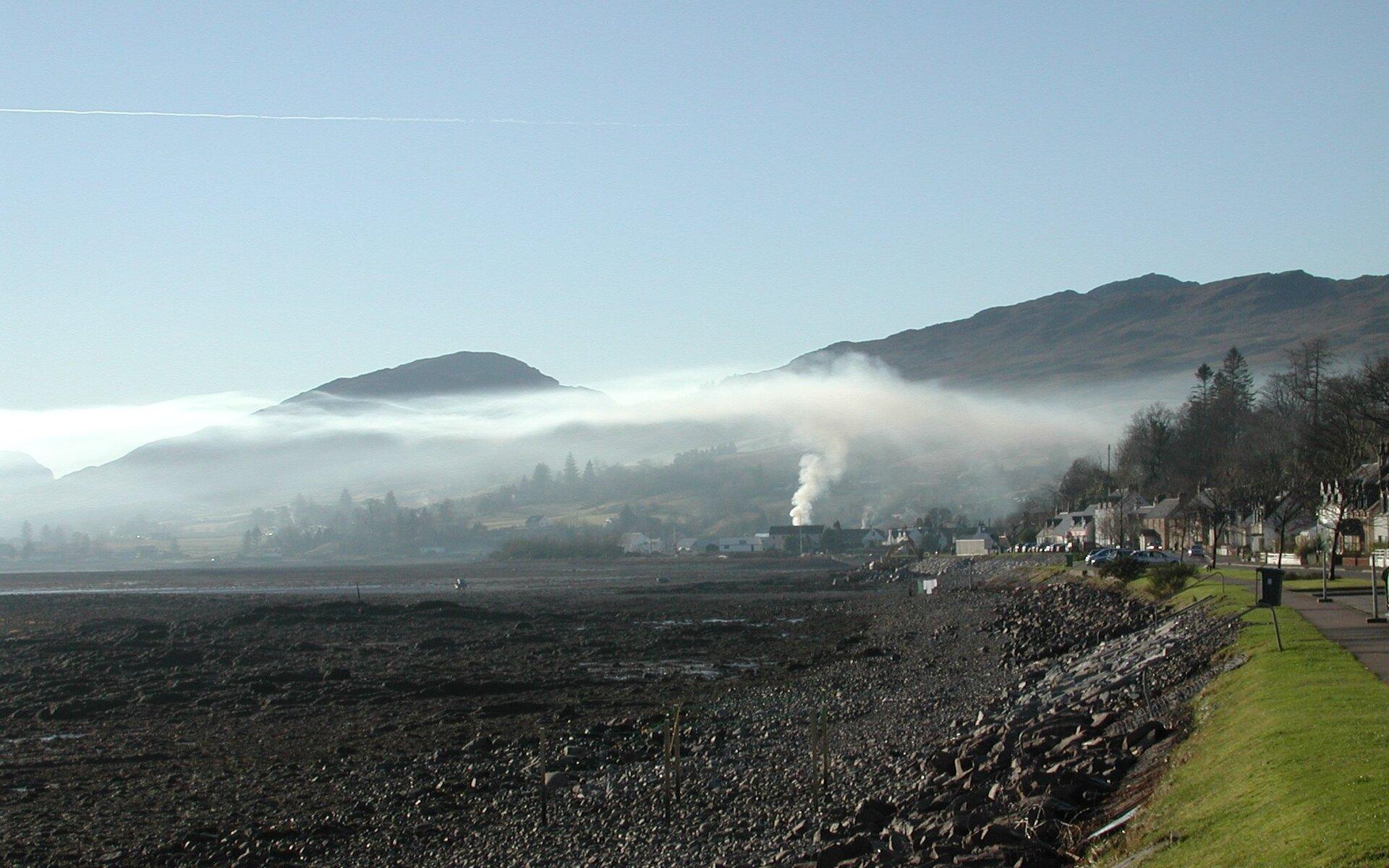 Zdjęcie krajobrazu. Na pierwszym planie błotnista ziemia. Zprawej strony droga itrawa. Wtle teren górzysty. Wcentralnej części dom, zkomina unosi się dym, do pewnej wysokości pionowo. Potem dym rozchodzi się wpoziomie. Dym zatrzymywany jest przez cieplejsze powietrze, wyjątkowo zalegające powyżej chłodniejszego powietrza.
