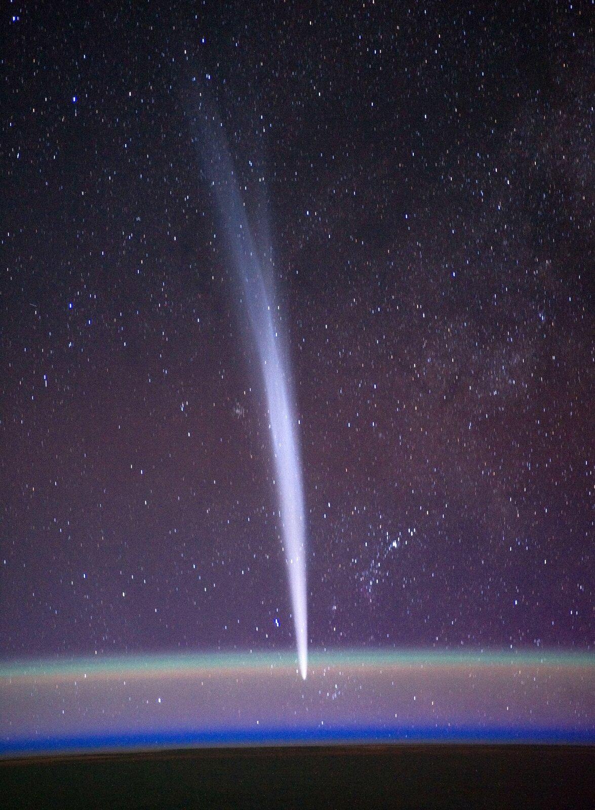 Fotografia przedstawia kometę na tle rozgwieżdżonego nieba. Na dole widać zaokrąglony koniec komety, czyli głowę. Ku górze zdjęcia widać warkocz komety mający postać świetlistego wachlarza, przez który prześwitują gwiazdy.