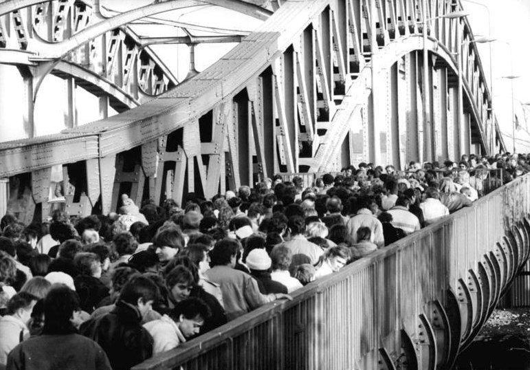 Tłum obywateli NRD na moście przed przejściem granicznym, 18 listopada 1989 Źródło: Robert Roeske, Tłum obywateli NRD na moście przed przejściem granicznym, 18 listopada 1989, Fotografia, Bundesarchiv, licencja: CC BY-SA 3.0.