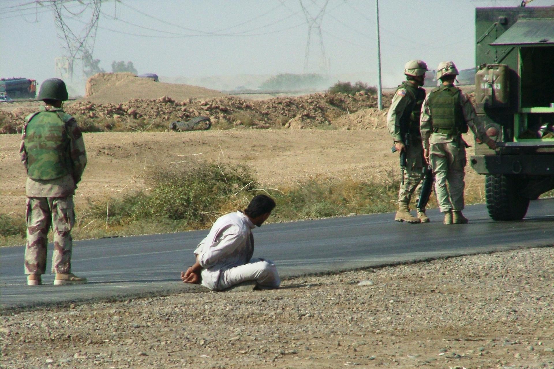 Zdjęcie przedstawia rezultat akcji schwytania terrorysty. Bliski Wschód. Asfaltowa droga na obrzeżach miasta. Po prawej stronie drogi wóz bojowy idwóch żołnierzy stojących obok wozu. Po lewej żołnierzy obserwujący teren. Na kamienistym poboczu siedzi schwytany związany Talib. Wgłębi zdjęcia słupy wysokiego napięcia.