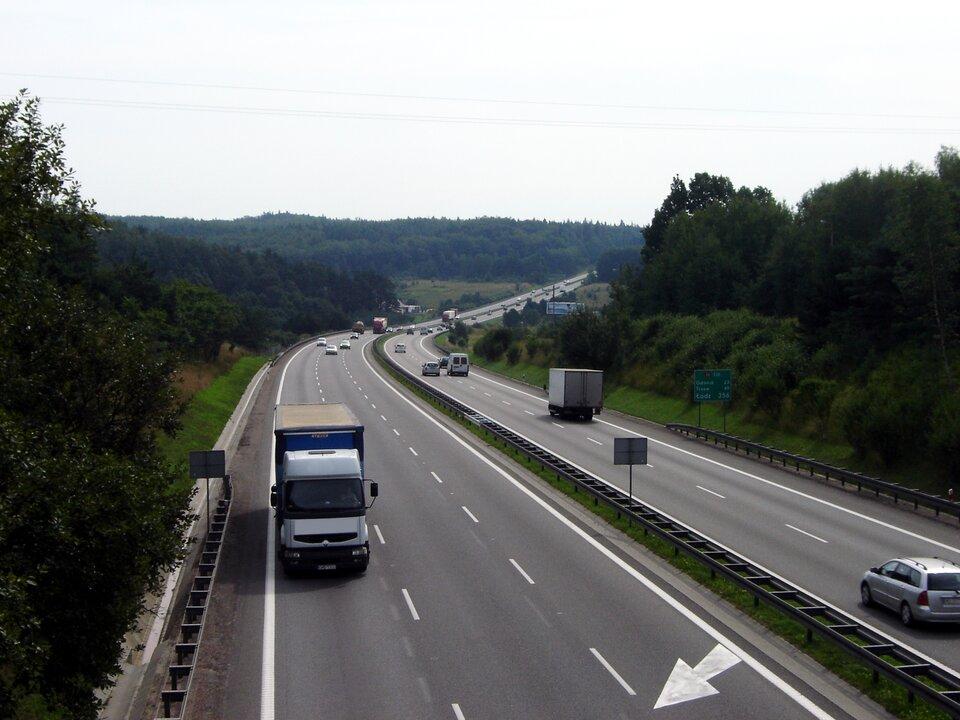 Fotografia prezentuje autostradę ztrzema pasami ruchu wobu kierunkach. Autostradą jadą samochody ciężarowe iosobowe. Pobocza autostrady porośnięte drzewami, krzewami itrawą.