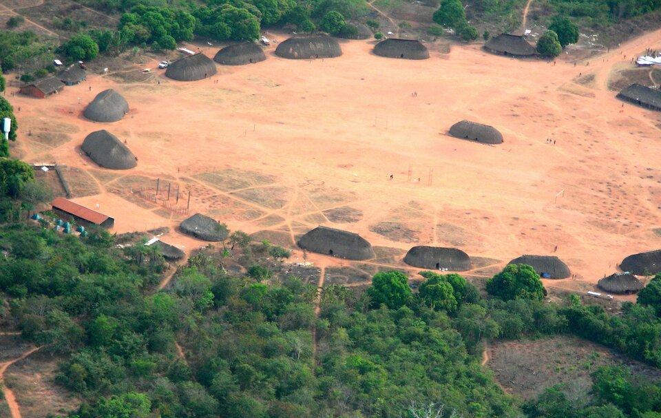 Na zdjęciu lotniczym okrągły piaszczysty teren wśrodku lasu. Dookoła ustawione jednakowe owalne chaty kryte słomą lub liśćmi. Jedna chata pośrodku. Dojazd do wioski zjednej strony.