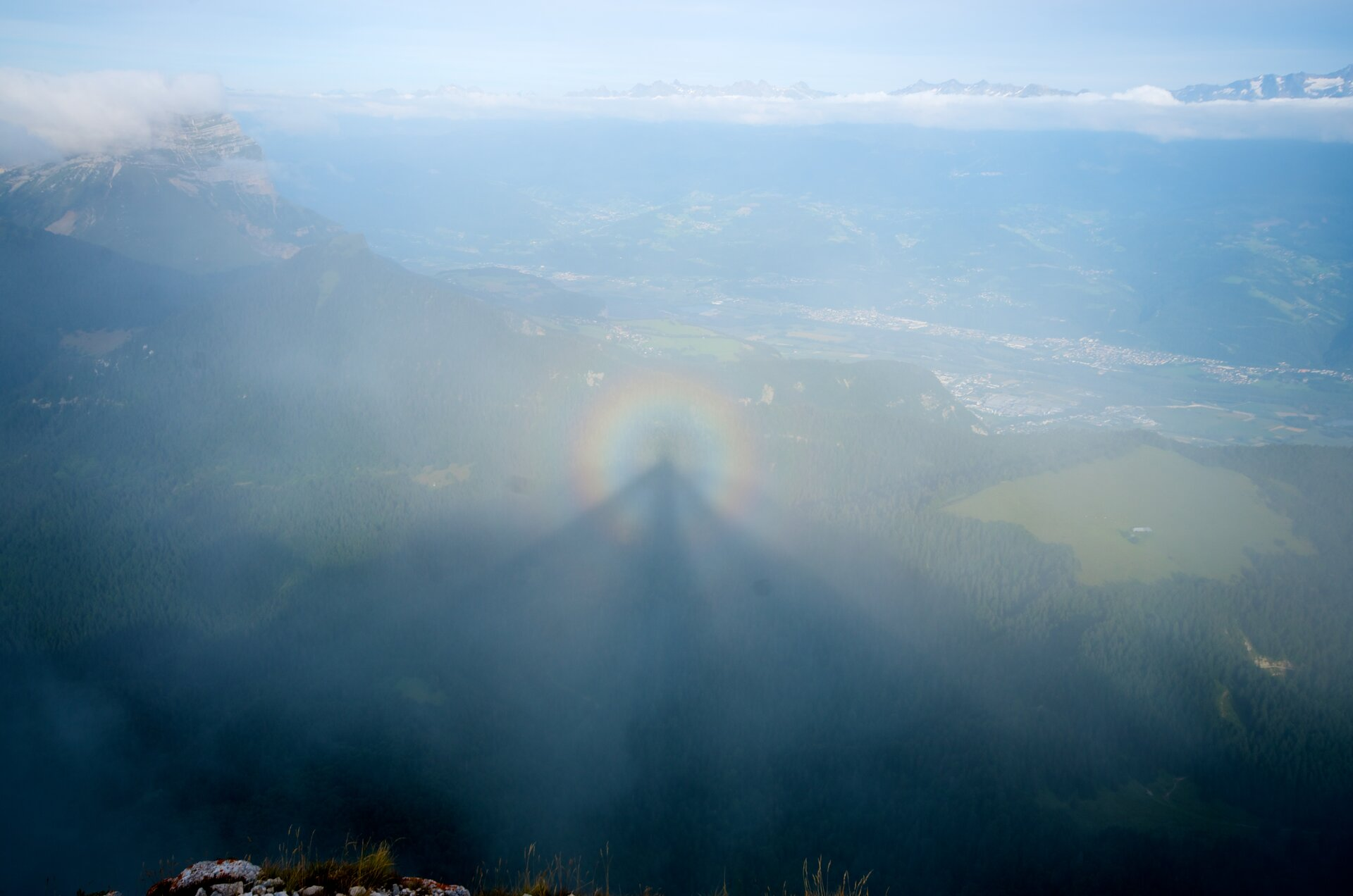 Fotografia prezentuje zjawisko optyczne spotykane wgórach, nazwane Widmem BrockenuNa fotografii widoczny cień osoby na chmurze, która znajduje się poniżej obserwatora. Cień otoczony jest tęczową obwódką zwaną glorią.