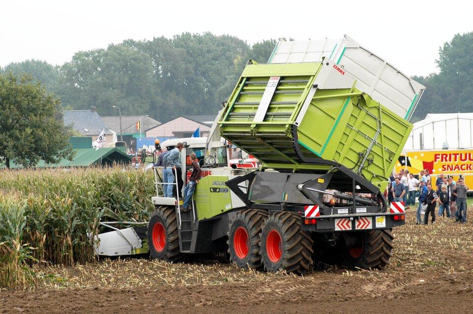 Na zdjęciu kombajn, zbierający kukurydzę. Na pierwszym planie odsłonięta gleba, mocno ugnieciona ciężkimi kołami kombajnu.
