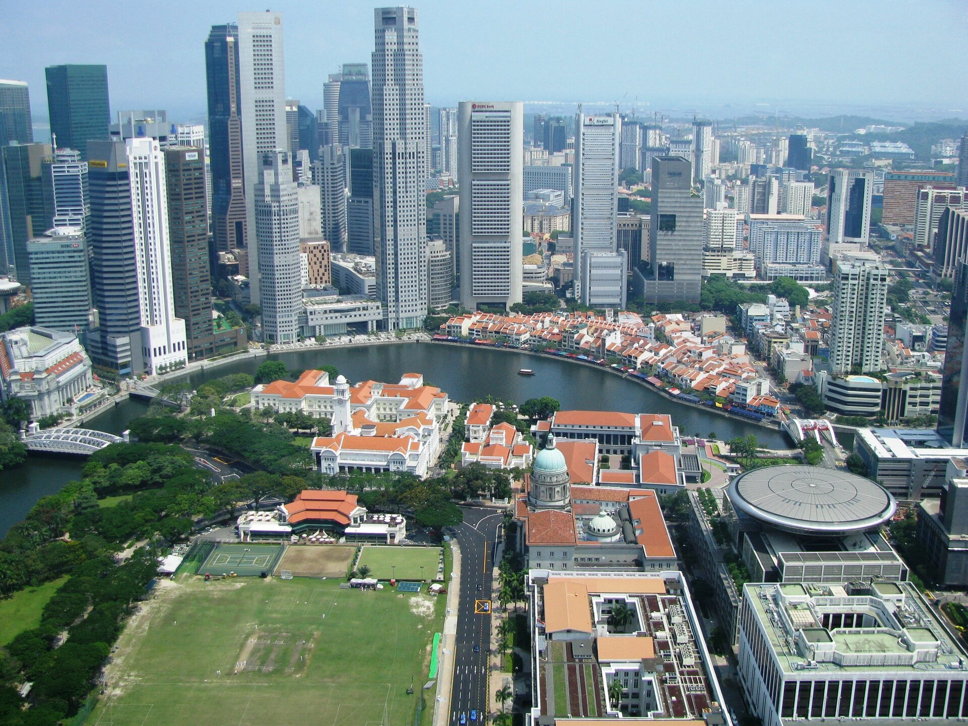 Na zdjęciu nowoczesne centrum biznesowe, wysokie biurowce, obok niska zabudowa, czerwone dachy. Rzeka, most.