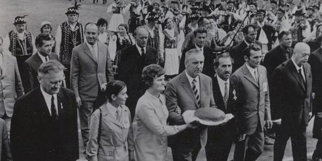 Fotografia czarno- biała przedstawiająca dożynki wczasach PRL. Edward Gierek, który przewodniczy pochodowi dożynkowemu otoczony tłumem współpracowników, działaczy niesie chleb.