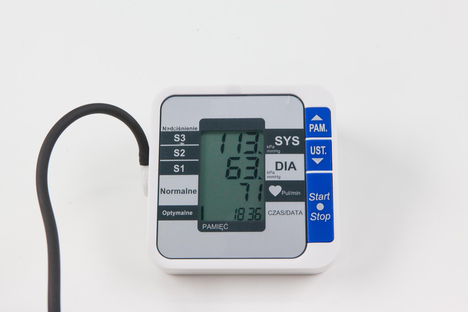 Fotografia przedstawia ciśnieniomierz elektroniczny do użytku domowego. Na ekranie urządzenia ugóry znajduje się wynik ciśnienia skurczowego (SYS). Niżej wynik pomiaru ciśnienia rozkurczowego (DIA). Jeszcze niżej symbol serca, ukazujący częstość pulsu. Zlewej przewód elektryczny. Zprawej niebieskie przyciski: pamięć, ustawienia iwskaźnik start – stop.