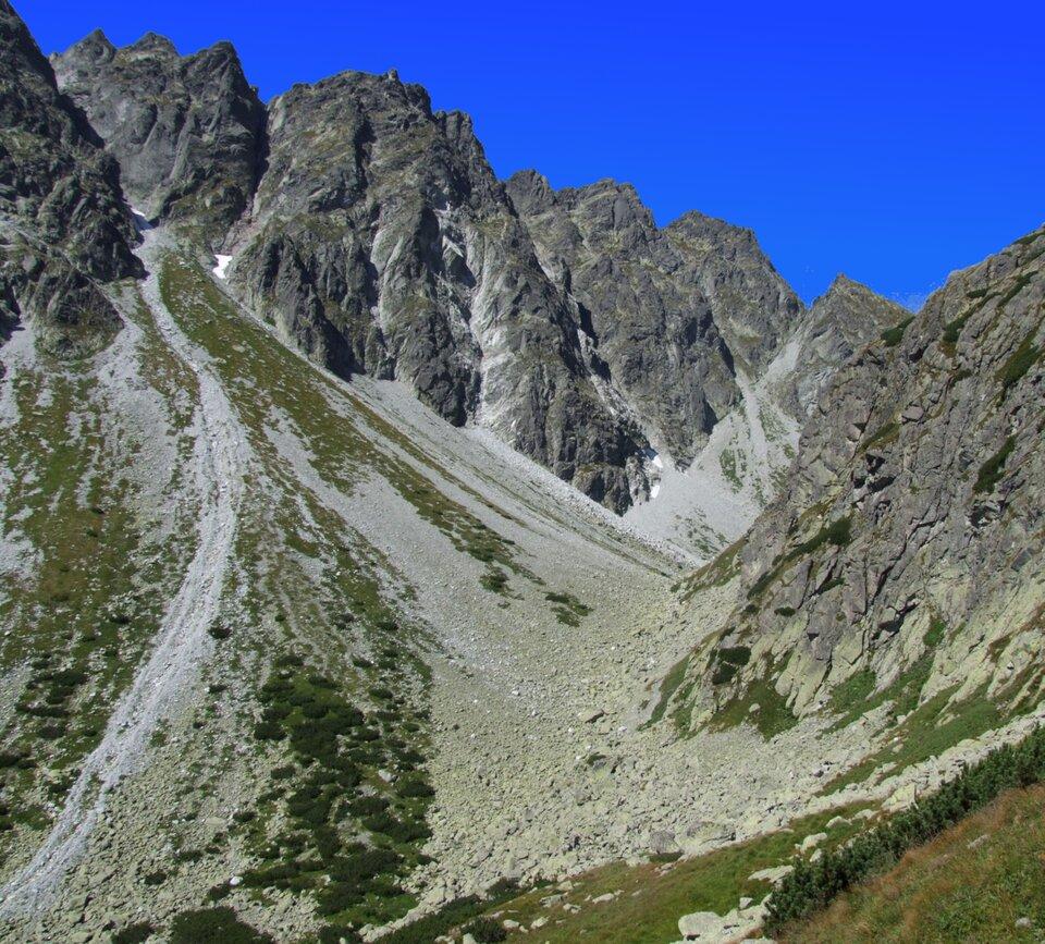 Ilustracja przedstawia fragment Tatr Wysokich. Na górze znajduje się postrzępiona grań, poniżej nagromadzony drobny materiał skalny pochodzący zniszczenia stoku.