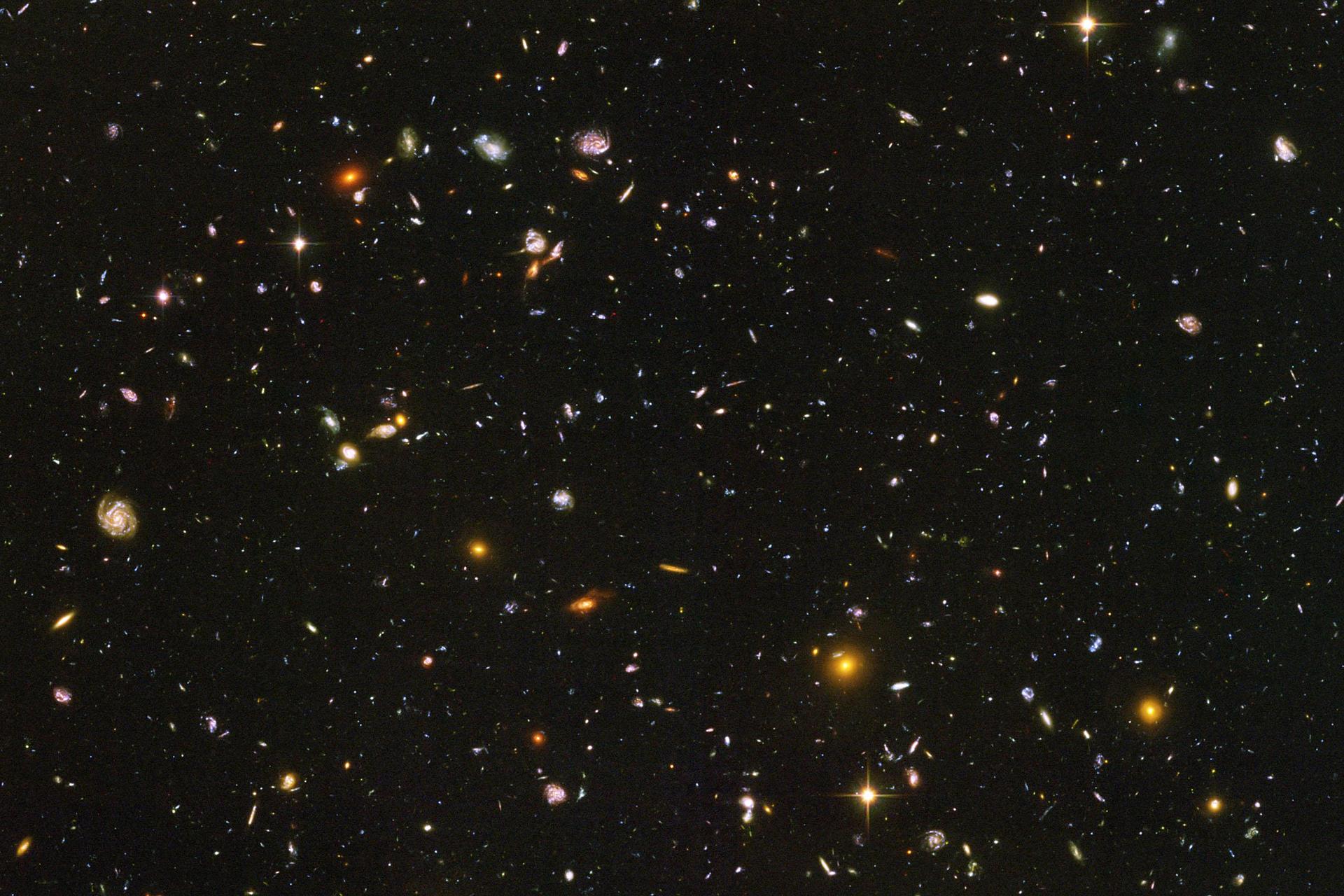 Fotografia wykonana zteleskopu umieszczonego wkosmosie. Na tle czarnego nieba widoczne liczne mniejsze lub większe punkty obrazujące galaktyki.