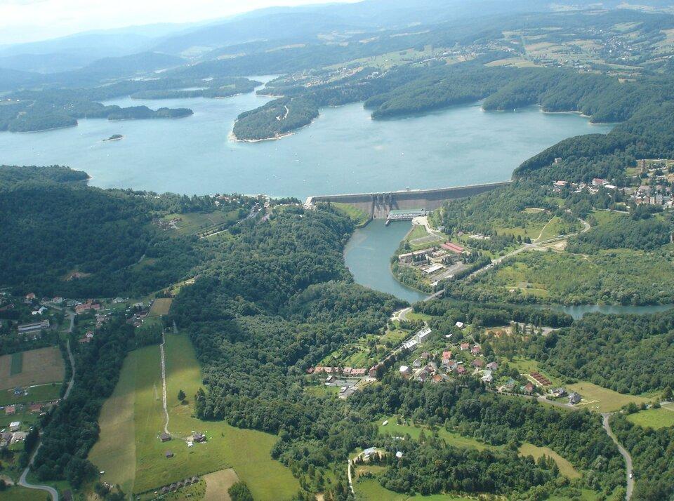 Na zdjęciu lotniczym zbiornik wodny onieregularnej linii brzegowej, porośniętej lasem, na pierwszym planie betonowa zapora, poniżej rzeka, zabudowania.