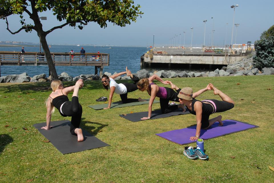 Fotografia przedstawia morskie nabrzeże. Na matach na trawie cztery kobiety wstrojach sportowych wykonują ćwiczenia. Aktywność fizyczna zapobiega chorobom serca.