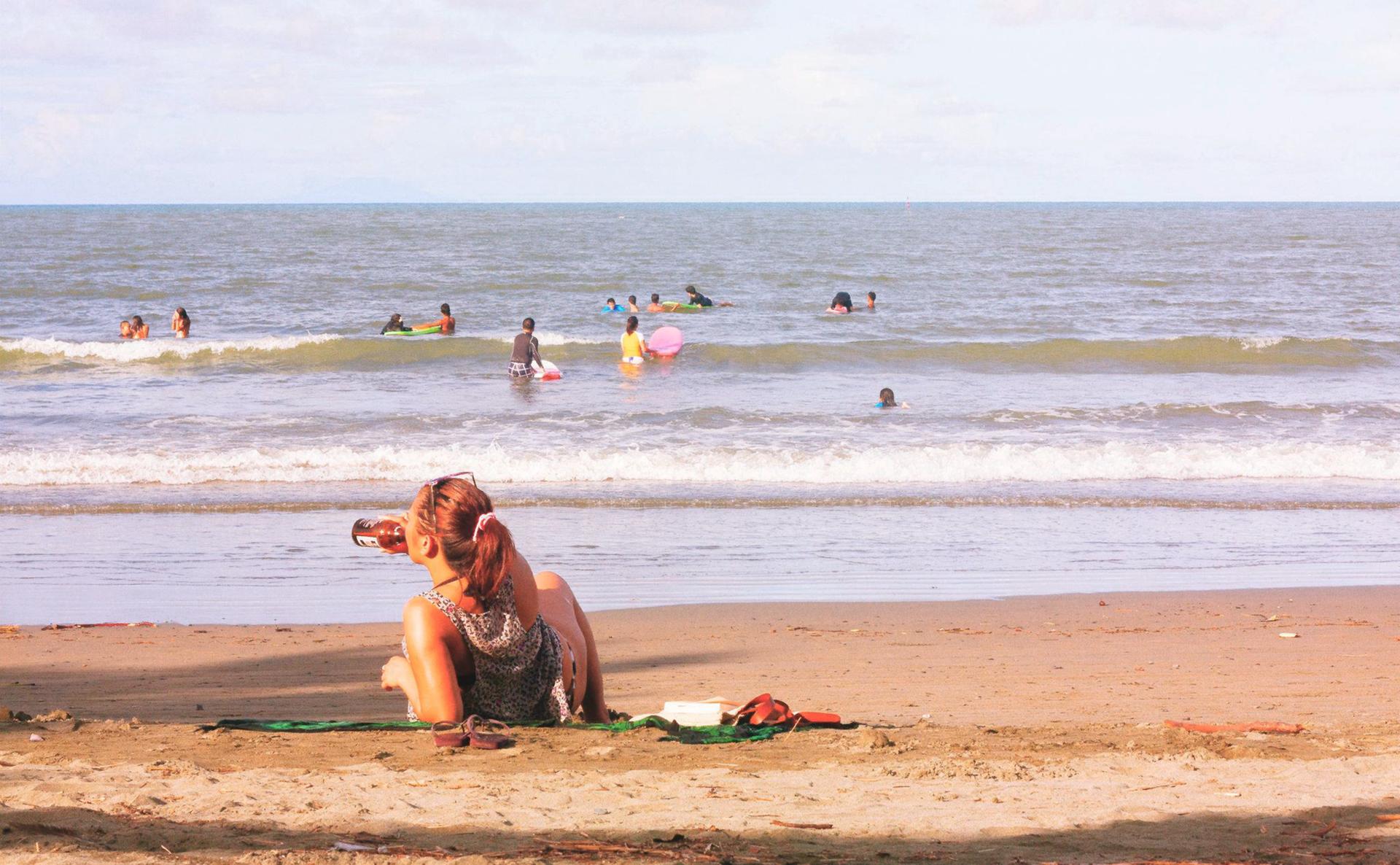Kolorowe prostokątne zdjęcie przedstawia słoneczny letni dzień na plaży. Na pierwszym planie młoda kobieta leży na kocu, na piasku. Wsparta na prawym łokciu. Wdrugiej ręce trzyma butelkę zpiwem. Pije piwo zbutelki. Wgłębi morze. Małe fale. Kilkanaście osób pływa wmorzu.