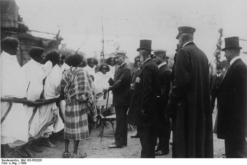 """Cesarz Wilhelm II wizytuje """"wystawę etnograficzną"""" Źródło: Cesarz Wilhelm II wizytuje """"wystawę etnograficzną"""", 1909, German Federal Archives, licencja: CC BY-SA 3.0."""