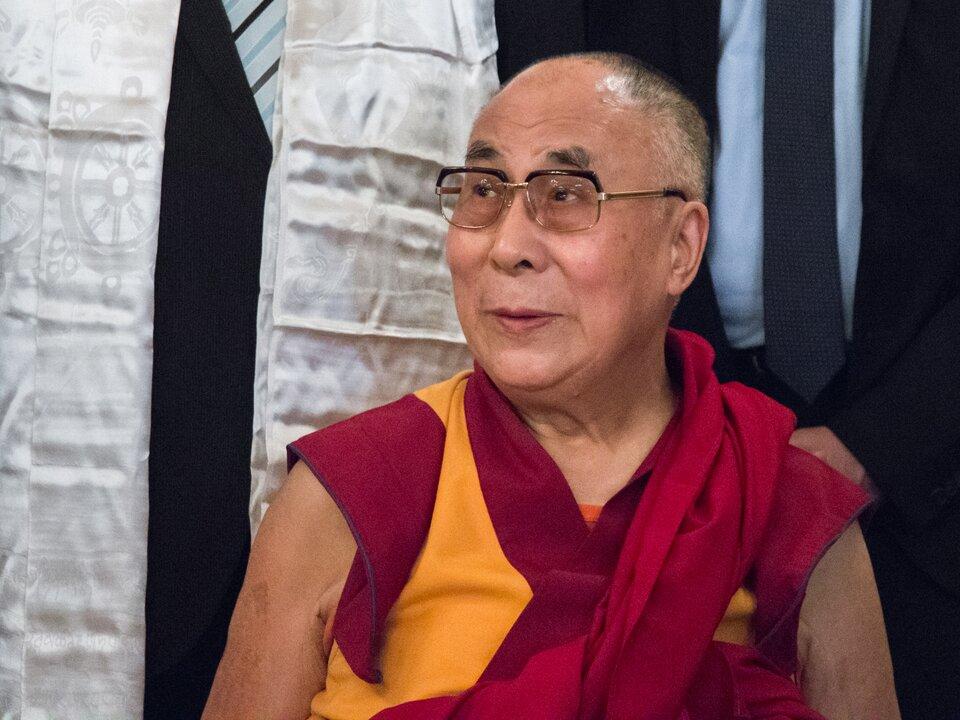 Na zdjęciu Dalajlama, mężczyzna wokularach, ubrany wżółto-czerwony strój.