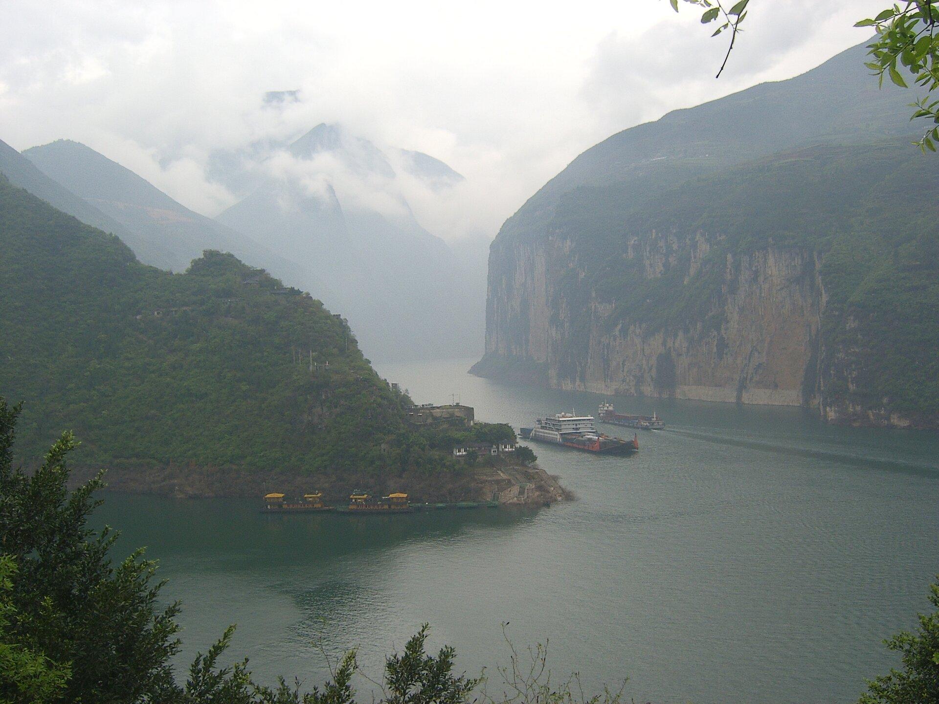 Na zdjęciu szeroka rzeka wkotlinie. Strome zbocza pokryte częściowo odsłonięte, częściowo pokryte bujną roślinnością. Po rzece płyną statki.