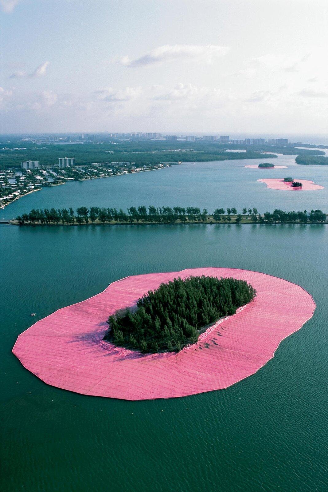 Ilustracja przedstawia różowy materiał okalający wyspę zdrzewami. Wtle widać inne wyspy ogrodzone wten sam sposób. Artyści otoczyli 11 niezamieszkałych wysp wpobliżu Miami różową tkaniną szerokości ok. 70 metrów.
