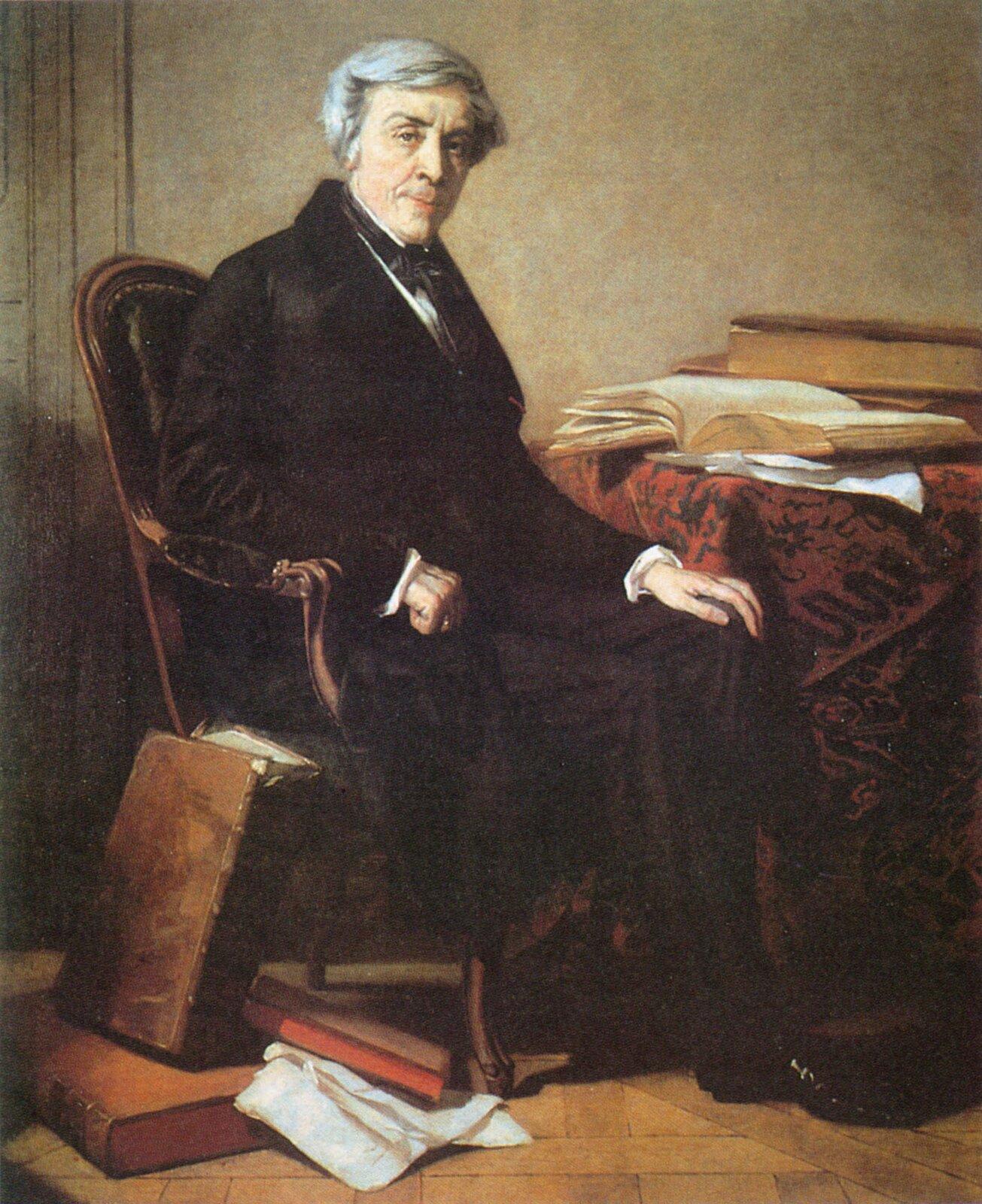 Siwowłosy mężczyzna ubrany wbrązowe ubranie siedzi na fotelu przy stole. Na stole leży czerwono-brązowy obrus. Wokół meżczyzny na biurku ina podłodze leżą porozkładane książki ikartki papieru.