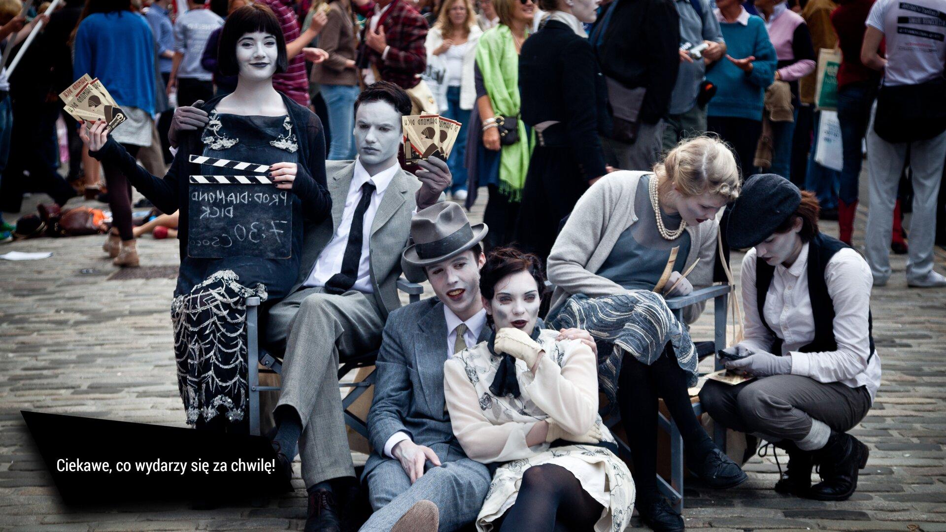 """Na ekranie wyświetla się zdjęcie, które przedstawia ludzi ubranych wstroje zIpołowy XX wieku. Są to dwaj mężczyźni icztery kobiety. Ich twarze są pomalowane na biało. Po lewej stronie zdjęcia, na krześle siedzi mężczyzna, ana oparciu kobieta. Trzymają ulotki wtaki sposób, wjaki trzyma się wachlarz. Po prawej stronie siedzą dwie kobiety. Jedna pokazuje coś drugiej. Wśrodku siedzi mężczyzna, który obejmuje kobietę. Być może są to aktorzy grupy teatru ulicznego. Za nimi widać tłum. Prawdopodobnie są to widzowie. Wlewym dolnym rogu na tle czarnego czworoboku widnieje biały napis otreści: """"Ciekawe, co wydarzy się za chwilę!""""."""