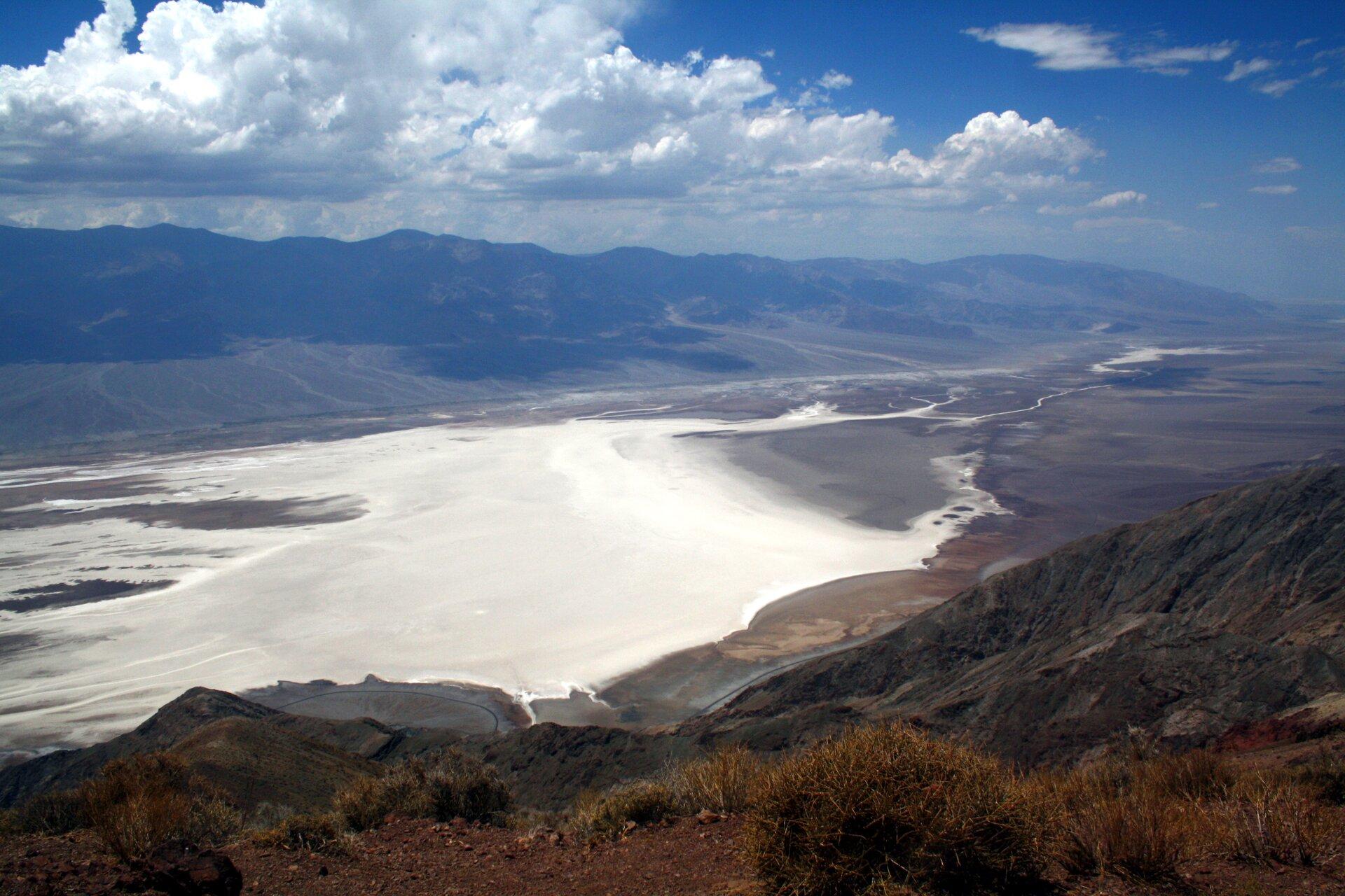 Na zdjęciu rozległa dolina wypełniona białym osadem. Dolinę otaczają potężne pasma górskie. Na pierwszym planie kępy traw. Niebo pokryte gęstym chmurami.