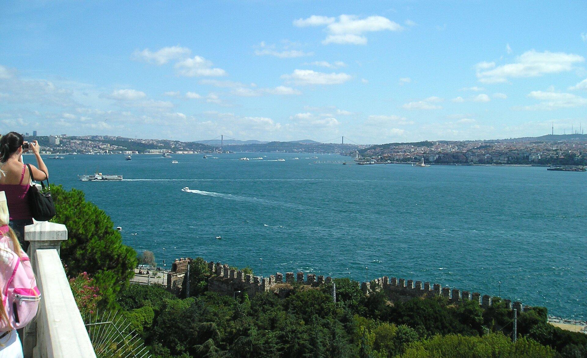 Na zdjęciu widok na zbiornik wodny. Statki, motorówki. Na pierwszym planie ludzie robią zdjęcia. Na drugim brzegu tereny gęsto zabudowane.