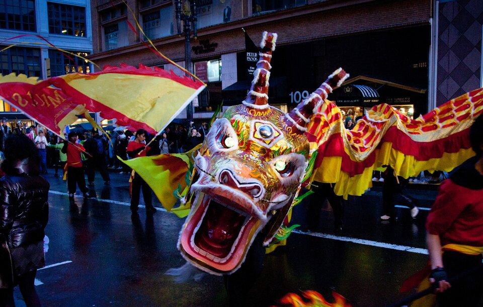 Zdjęcie przedstawia obchody chińskiego Nowego Roku. Wieczór. Centrum miasta. Wzdłuż ulicy korowód świętujących mieszkańców. Wśrodku korowodu kolorowy chiński smok. Głowa smoka skierowana wkierunku obserwatora. Otwarta paszcza ukazuje zęby. Na głowie duże czerwone stożkowate rogi. Za głową długi wężowaty tułów smoka. Tułów widoczny wprawej części zdjęcia. Długi tułów tworzą osoby idące jedna za drugą wodległości metra. Osoby zasłonięte są kolorowym materiałem imitującym skórę smoka. Boki smoka tworzy materiał wkształcie falbanek. Falbany uszyte zpoziomo zszytych pasów. Na górze czerwony, poniżej żółty. Cały smok jest wkolorze żółtym iczerwonym. Na lewo od smoka trzej mężczyźni niosą olbrzymie flagi. Flagi wkształcie trójkąta. Wnętrze wkolorze żółtym. Poziome krawędzie obszyte na czerwono.