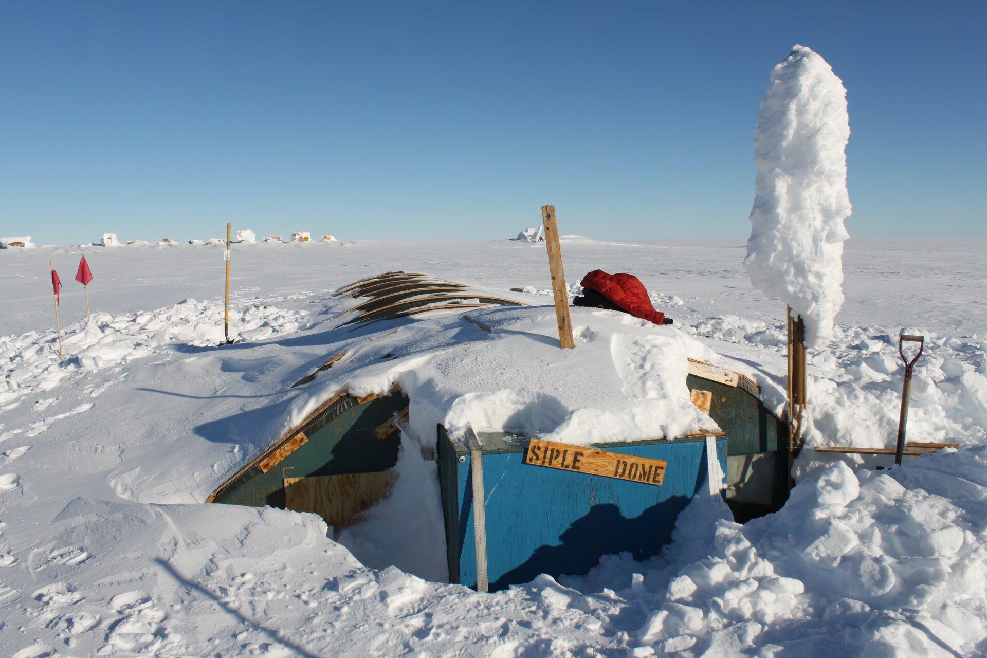 Na zdjęciu zabudowania niemal całkowicie przysypane śniegiem. Widoczny jedynie niewielki fragment namiotu wobozie antarktycznym. Na drugim planie teren całkowicie pokryty śniegiem. Dwie czerwone flagi wbite wśnieg, łopata wbita wśnieg.