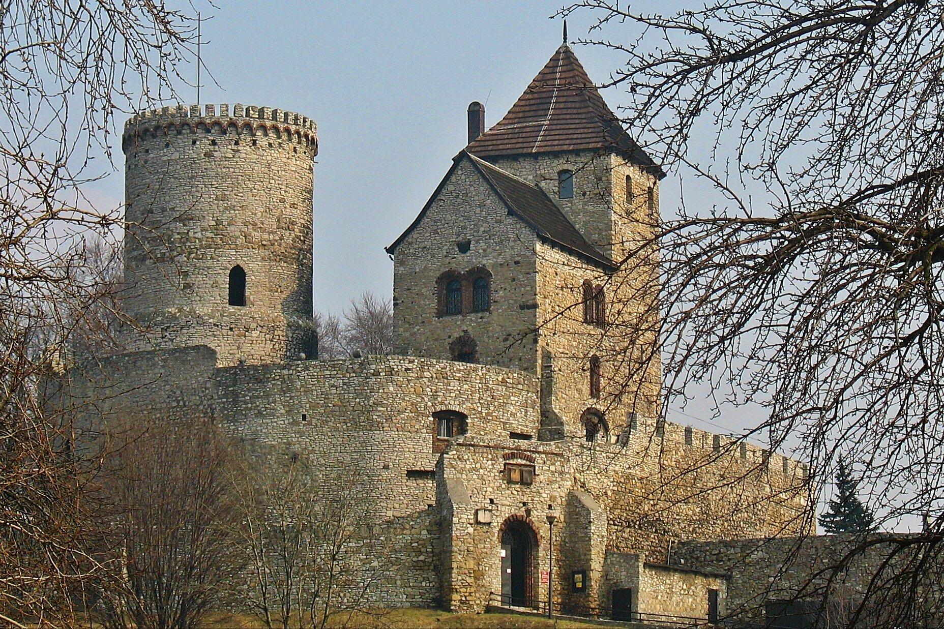 Otoczone szarymi, kamiennymi murami obronnymi zabudowania ibaszta. Wcentralnej części brama wjazdowa do zamku. Za murami zabudowania ze szpiczastymi dachami pokrytymi czerwoną dachówką.