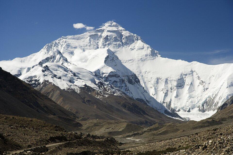 Zdjęcie przedstawia pasmo górskie. To fragment najwyższych gór świata Himalajów. Pasmo górskie pokryte jest śniegiem. Wśrodkowej części pasma najwyższy szczyt wkształcie trójkąta. To Mount Everest, najwyższa góra świata. Skalisty, pokryty śniegiem ioświetlony promieniami słonecznymi szczyt góry kontrastuje zkamienistym, brązowym terenem rozpościerającym się ustóp Mount Everestu. Wdole ilustracji widoczne ścieżki. Niebo błękitne.