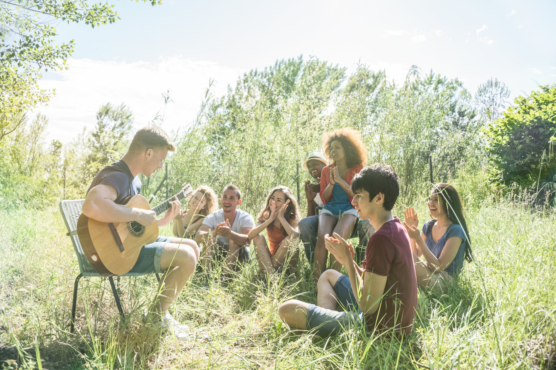 Ilustracja przedstawia grupkę przyjaciół na łonie natury. Jeden zmężczyzn po lewej stronie siedzi na krześle ogrodowym igra na gitarze, wokół niego znajdują się nastolatkowie, którzy się uśmiechają iklaszczą.