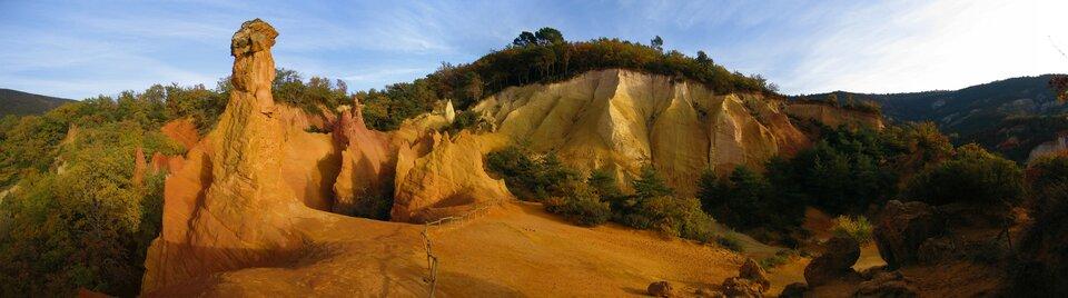 Na zdjęciu odkryta gleba typu terra rosa, koloru pomarańczowego, wtle porośnięte roślinnością pofałdowane góry.