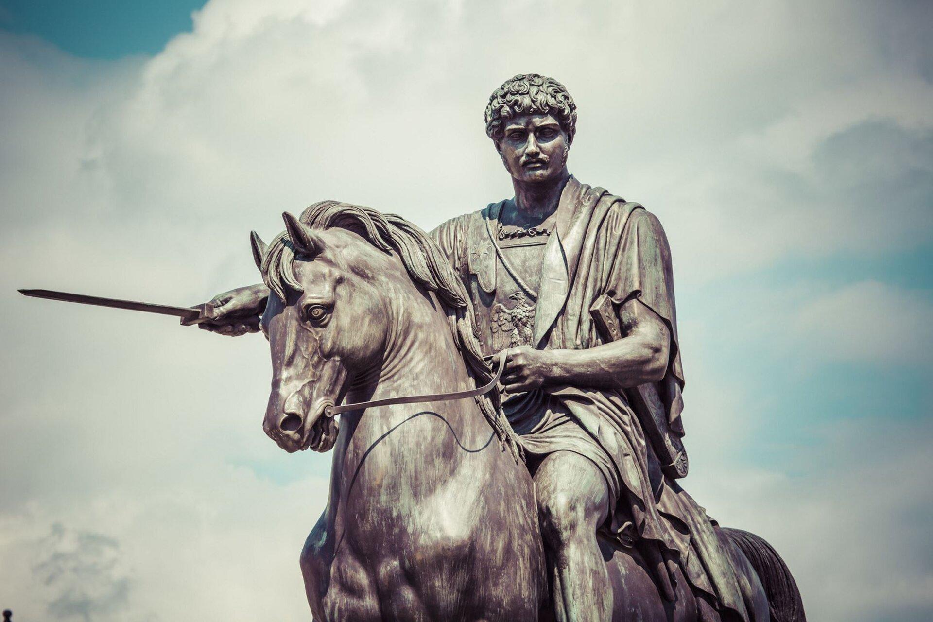 """Ilustracja przedstawia dzieło Bertela Thorvaldsena """"Pomnik księcia Józefa Poniatowskiego"""", ustawioną na postumencie. Ukazuje mężczyznę siedzącego na koniu. Wlewym ręku trzyma uprząż. Jego głowa jest lekko obrócona wlewo. Za pomnikiem tło wypełnia błękitne niebo."""