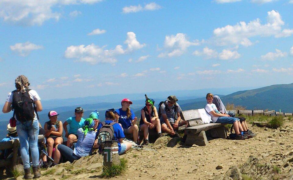 Na zdjęciu grupa młodzieży na górskim szlaku. Siedzą na ławkach iziemi, kolorowa ubrani. Lato. Wtle rozległe tereny górskie.