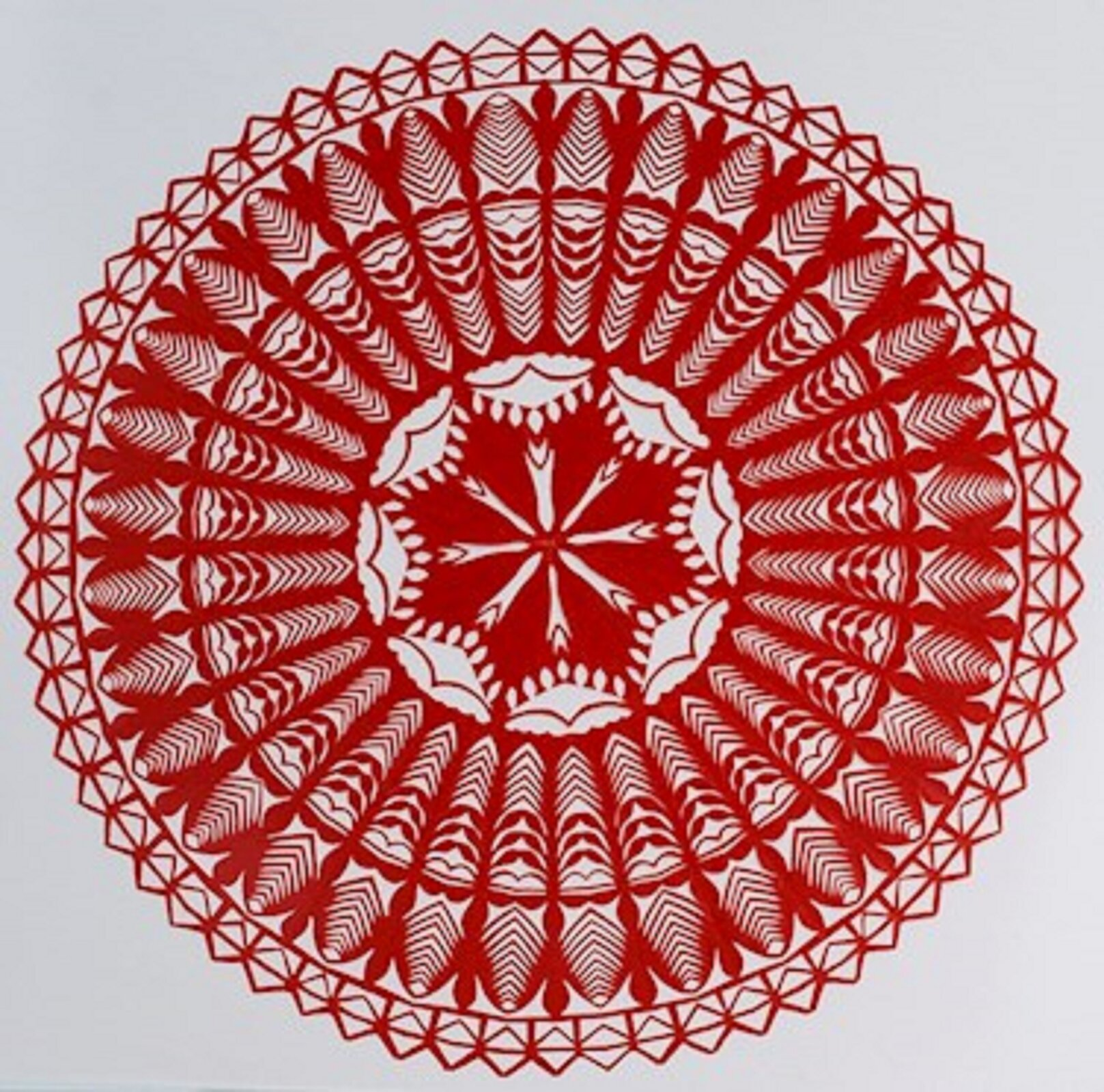 Ilustracja przedstawia kurpiowską gwiazdę. Wzór jest wykonany wkolorze czerwony. Składa się ztrzech pierścieni oróżnej grubości ikola wśrodku. Zewnętrzny pierścień dookoła to ułożone obok siebie otwarte koperty. Każdy pierścień ma inny wzór, aśrodek to gwiazda oośmiu wierzchołkach.