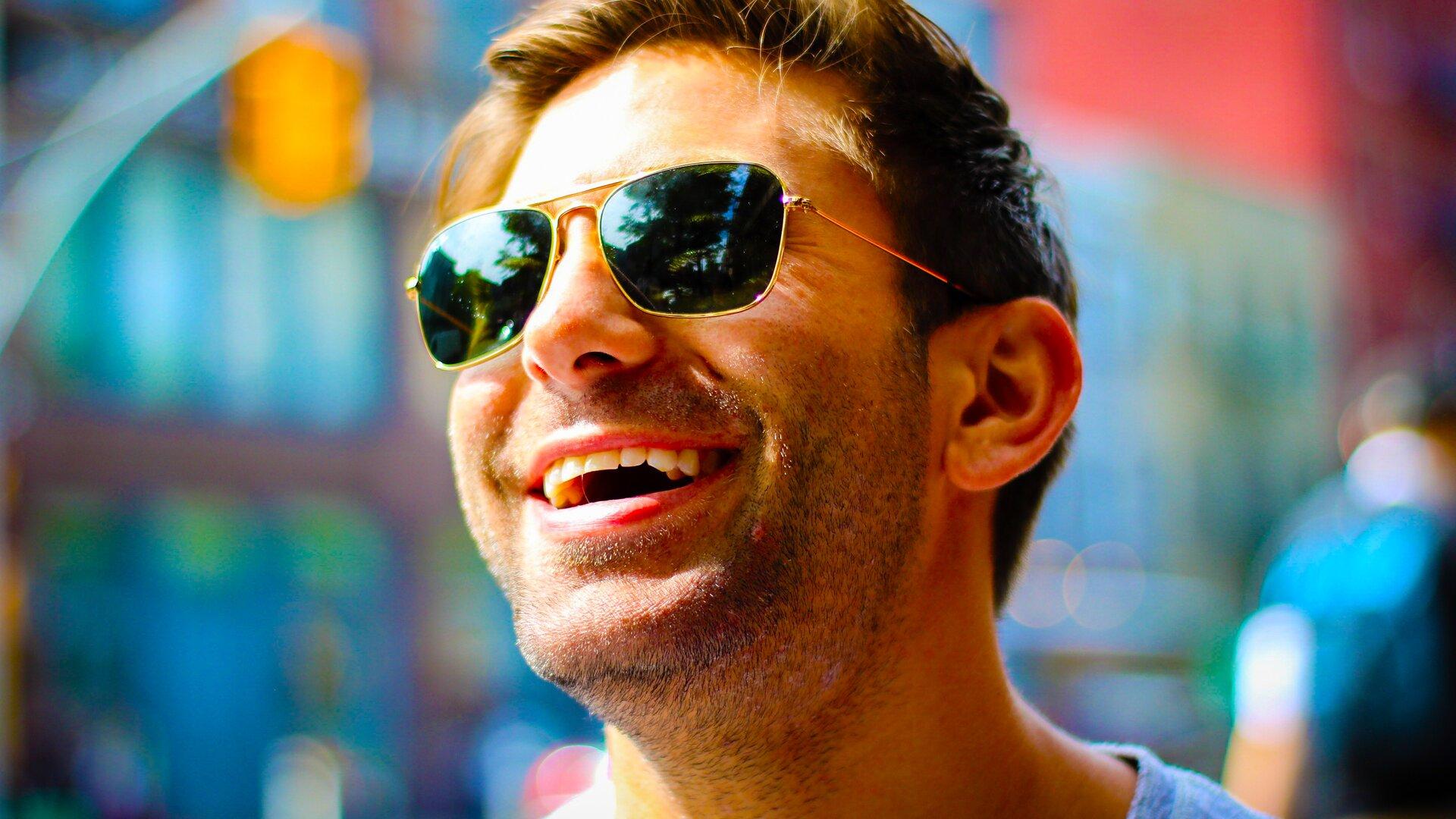 Ilustracja przedstawia uśmiechniętego mężczyznę. Mężczyzna jest średniego wieku, jest brunetem, nosi kilkudniowy zarost. Na nosie ma okulary.