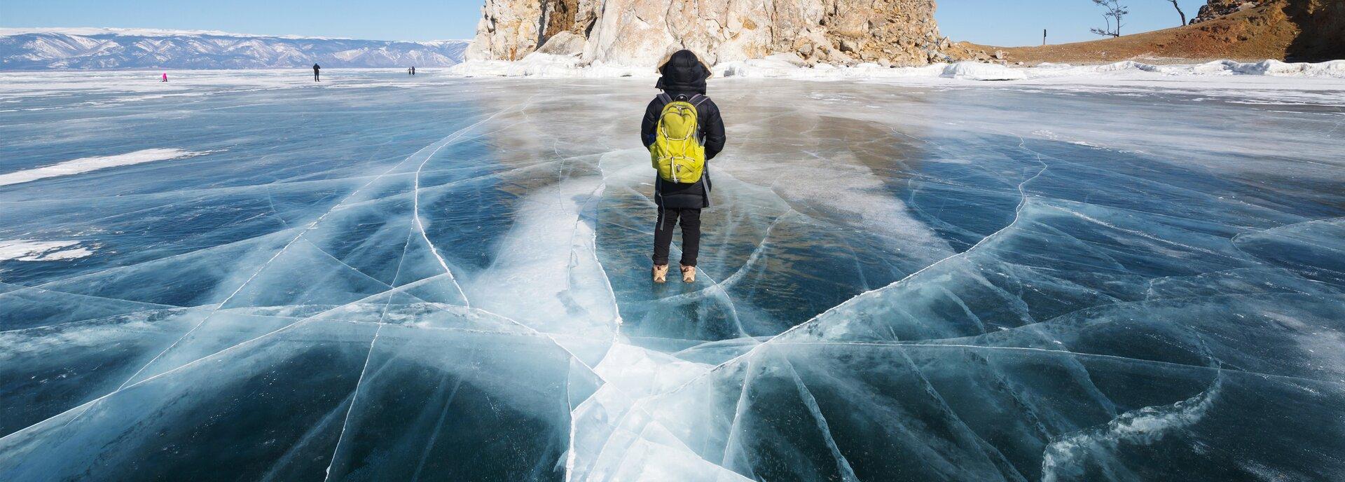 Kolorowe zdjęcie przedstawia zamarzniętą taflę jeziora, na której widoczne są pęknięcia ibiałe rysy. Wcentralnej części zdjęcia, na środku, tam gdzie jest najwięcej pęknięć irys, na zamarzniętej tafli jeziora stoi tyłem człowiek ubrany wczarną kurtkę zkapturem nałożonym na głowę. Ma jasne zimowe buty, na plecach żółty plecak. Przed nim, woddali, widoczna jest skalista góra – na zdjęciu przedstawiono tylko jej podstawę. Woddali po lewej stronie znajdują się góry. Po prawej stronie skały widoczna jest brązowa ziemia – brzeg jeziora.