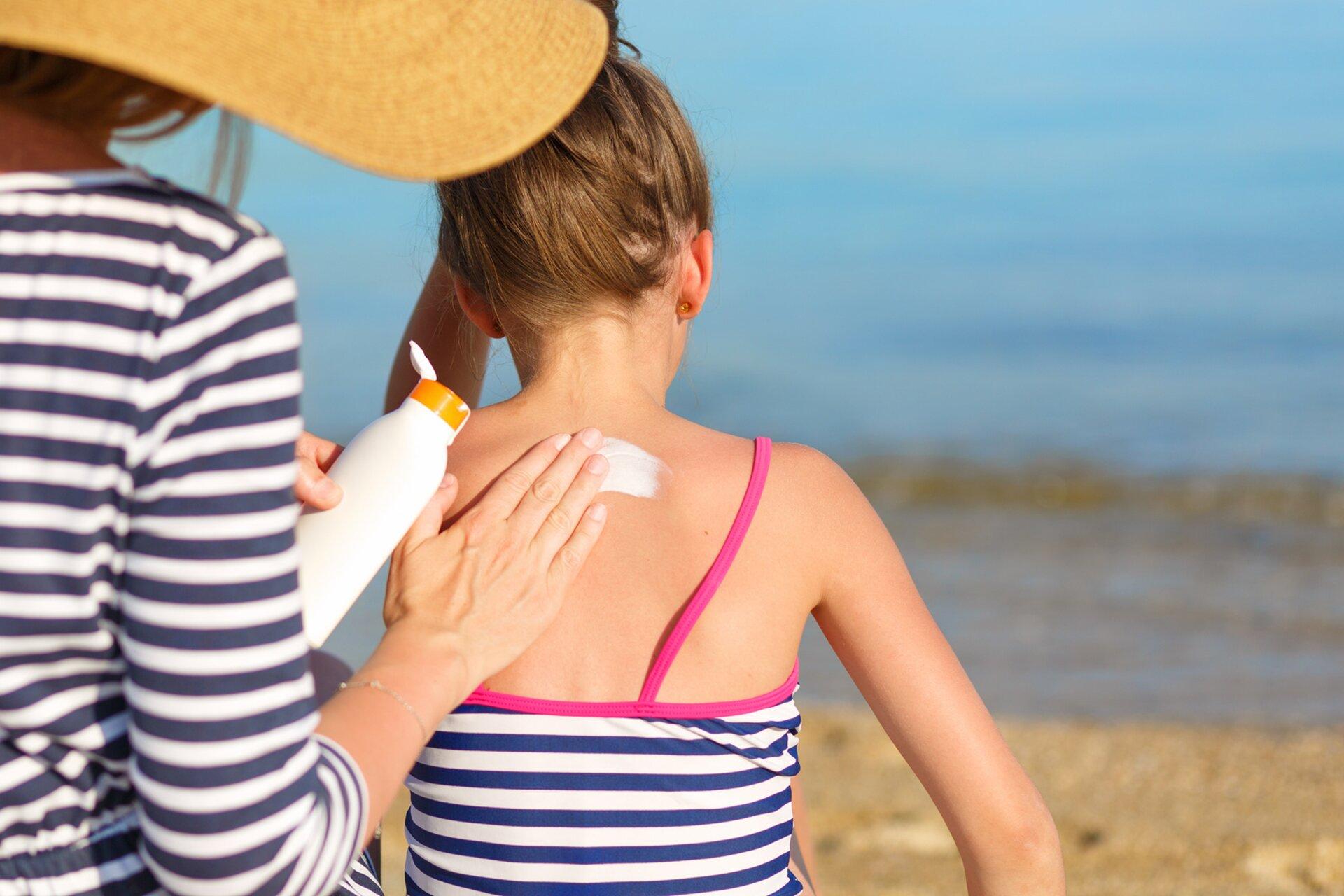 Fotografia prezentuje kobietę idziewczynkę siedzące na plaży. Kobieta smaruje białym kremem plecy dziewczynki.