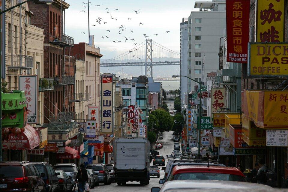 Na zdjęciu ulica wmieście. Liczne szyldy ireklamy znapisami wjęzyku chińskim. Wtle most.