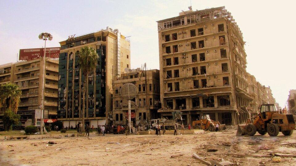 Na zdjęciu zniszczone budynki bez szyb woknach. Na ulicy spycharki iciężarówki.