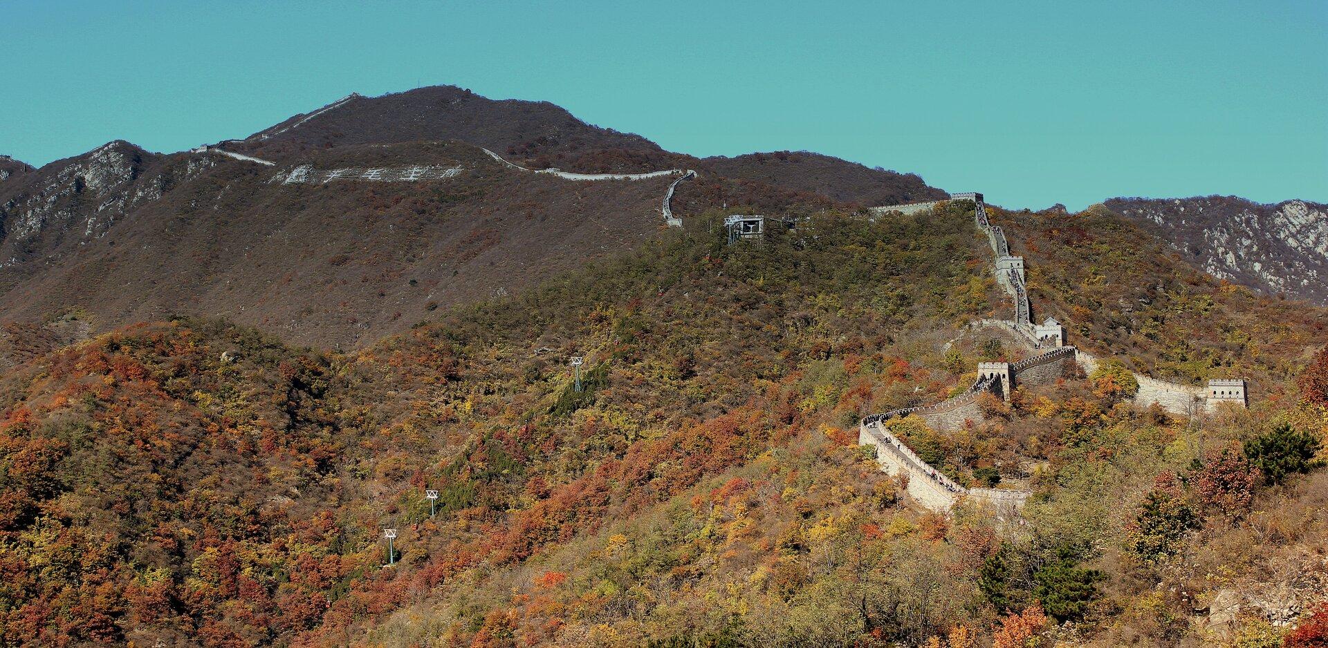 Na zdjęciu góry. Stoki gór widocznych na pierwszym planie pokrywa roślinność – las liściasty podczas jesieni. Kolory zielone, żółte, czerwone ibrązowe. Wyższe partie gór słabiej pokryte roślinnością. Wzdłuż górskich szczytów wysoki iszeroki mur. Na murze droga, po której spacerują turyści. Co kilkaset metrów na murze jest wieża obserwacyjna.